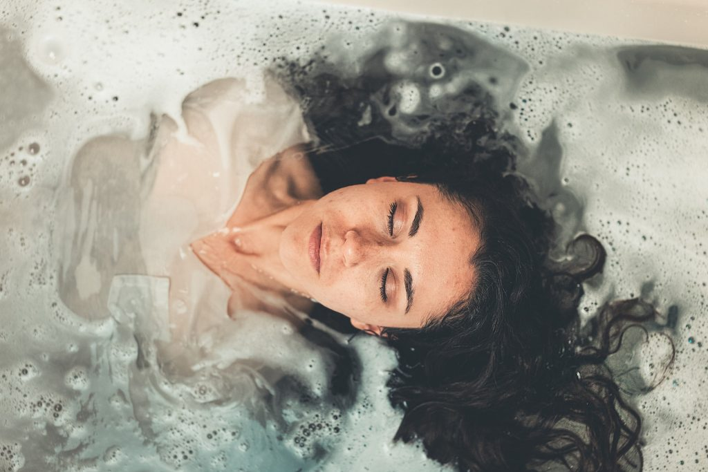 Picture of a woman in the water and her face just above the surface, eyes closed.